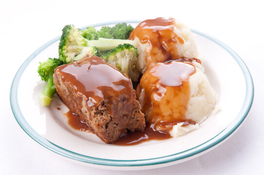 Meatloaf with mashed potatoes, gravy, and fresh vegetables