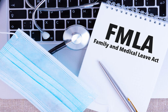 FMLA Family Medical Leave Act, the text is written in a notebook, next to a pen, a disposable medical mask and a laptop on a linen background.