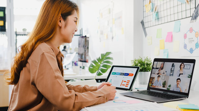 Asia businesspeople using laptop talk to colleagues discussing business brainstorm about plan in video call meeting in new normal office. Lifestyle social distancing and work after corona virus.