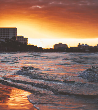 Wavy seascape with awith a majestic sunset view over urban city buildings