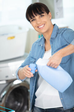 happy funny woman showing washing machine laundry liquid