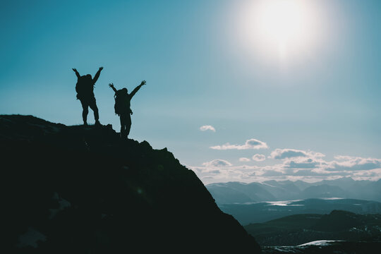 Silhouettes of two hikers on mountain top