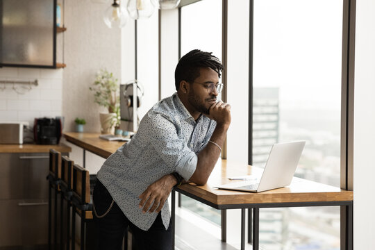 I need to think a little. Concentrated young black male ponder before pc screen at modern studio make important choice decision. Focused afro american guy study data or web search result using laptop