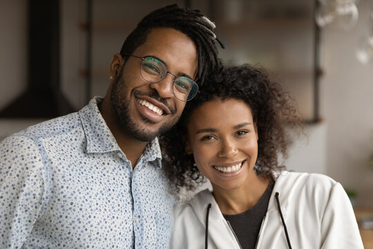 Sweet moment. Headshot family portrait of loving millennial black couple husband and wife hugging with warmth looking at camera demonstrating happy white smiles. Close relationship. Strong marriage