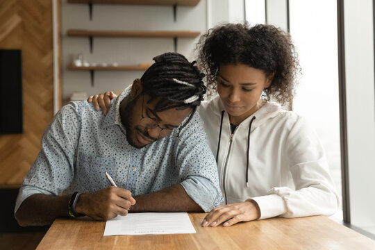Focused young black couple signing prenuptial agreement in lawyer office. Concentrated millennial afro husband wife insuring life property read paper document before write names and certify contract
