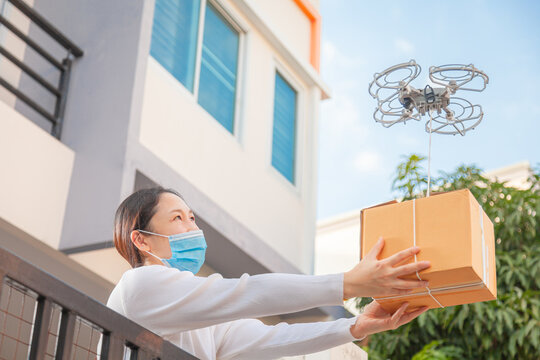 Drone delivery delivering parcel package into urban city. UAV drone deliver give to female costumer in front of home. Online shopping and Express delivery transport service concept,