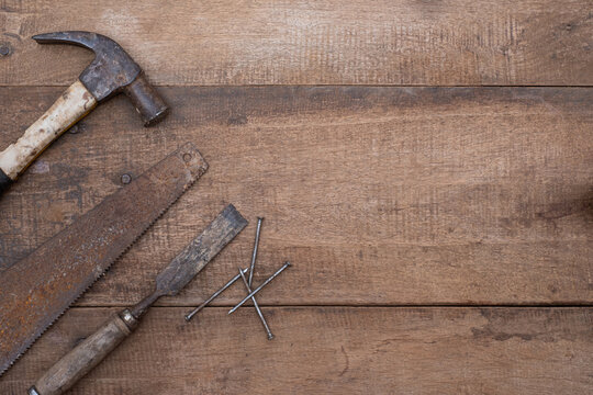Saw hammer and chisel collection of old woodworking handtools on a rough workbench wooden