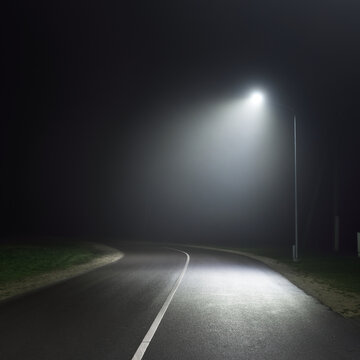 An empty motorway with a sharp turn in a fog at night. Road sign close-up. Dark urban scene, cityscape. Riga, Latvia. Dangerous driving, speed, freedom, concept image