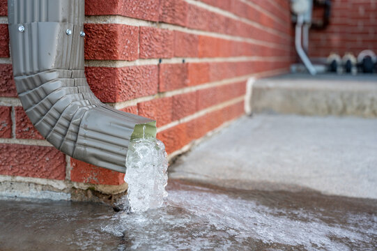 Metal downspout jammed with a frozen ice block