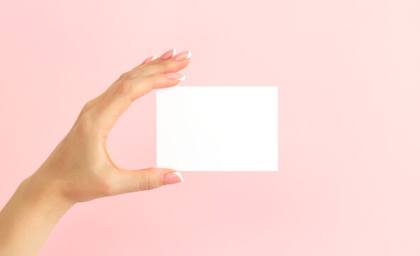Woman hand holding blank white mock-up card on pink background