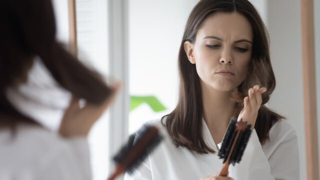 Unhappy upset millennial Caucasian woman brush long hair frustrated by hairloss or damaged thin split ends. Sad young female do hairstyle dissatisfied with hair breakage, need mask or treatment.
