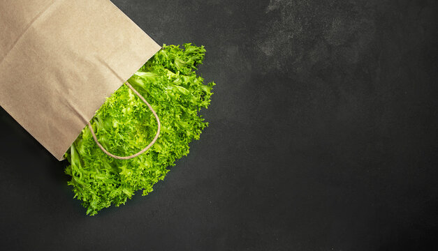 Curly green lettuce leaves in a paper bag on a dark background.