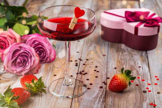 Pink roses, glass of strawberry margarita and heart shaped gift box on wooden plank background. Greeting card for Valentine's day, March 8th or mother's day. Wooden background. Copy space