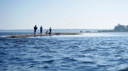 Ujęcie od strony morza piaszczystego półwyspu w miejscowości Rewa wraz ze spacerującymi po nim...
