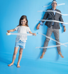 Funny portrait of a father being stuck to the wall by daughter