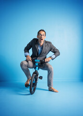 Portrait of a father riding a too small bike