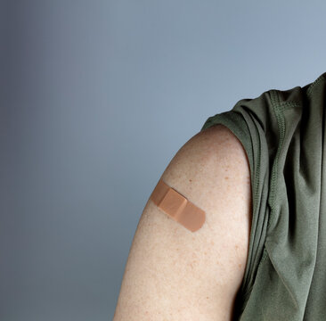 Band aid on male upper arm after covid 19 vaccine shot