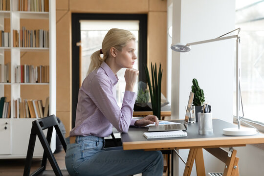 Pensive female entrepreneur looking at window and thinking of small company future. Thoughtful young businesswoman planning problem solving and strategy, feeling doubts, concerned about project issues