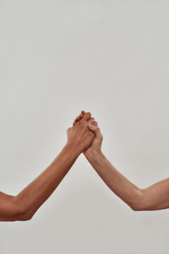 Close up of two hands holding each other, gesture of support isolated over light background