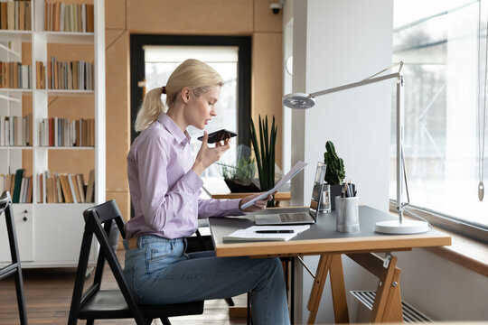 Female millennial entrepreneur giving command to virtual assistant on cellphone, using voice recognition, recording audio message, speaking at mic, reading document aloud, using speaker mode for call