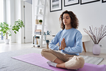 Healthy serene young woman meditating at home with eyes closed doing pilates breathing exercises, relaxing body and mind sitting on floor in living room. Mental health and meditation for no stress.