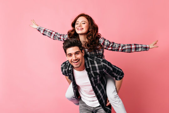 Excited girl in checkered shirt having fun with boyfriend. Young couple celebrating valentine's day.