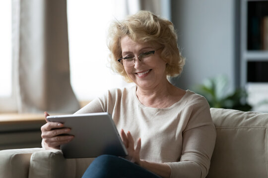 Happy middle aged older retired woman in eyeglasses using modern digital computer tablet, relaxing on sofa. Smiling senior granny enjoying web surfing or shopping online, easy technology usage.
