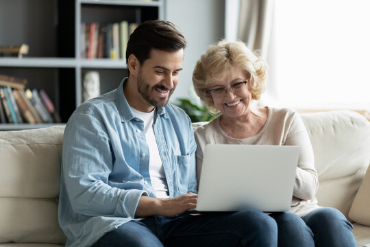 Happy young man teaching smiling older retired mother using computer software applications at home. Joyful different generations family looking at laptop scree, enjoying web surfing or shopping online