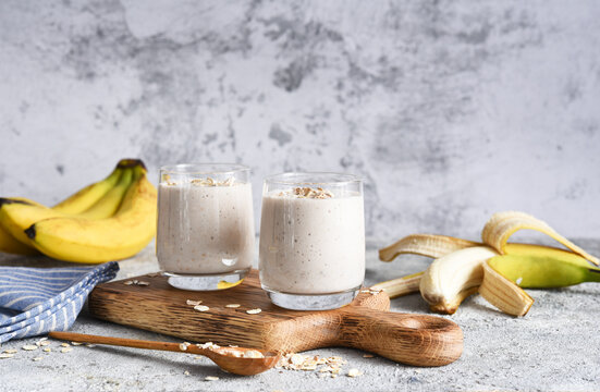 Smoothie with banana and oatmeal for breakfast on a light concrete background. Detox menu.