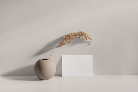 Modern summer stationery still life scene. Beige spheric vase with dry lagurus grass. Table background in sunlight. Blank paper card, invitation mockups lean on champagne wall, long shadows.