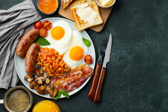 Full English breakfast on a plate with fried eggs, sausages, bacon, beans, toasts and coffee on dark stone background. With copy space. Top view