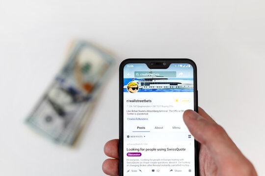 Minsk, Belarus - 31, January, 2021: Reddit logo on smartphone screen in male hands with money on table