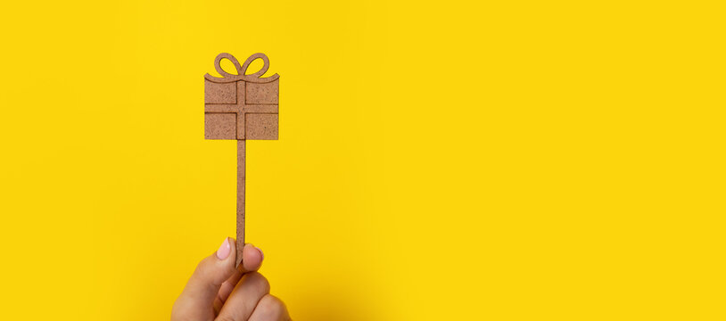 wooden gift in hand over yellow background