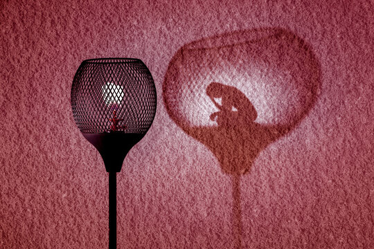 Gaslight with silhouette of woman in shadow cast by the lamp on wall, Gaslighting concept illustration