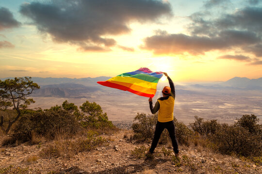 Back view of a man standing on top of the hill and holding the LGBT pride flag