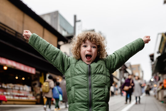 Portrait of an excited young boy on vacation, standing in Omotesando Street, Narita City, Japan.