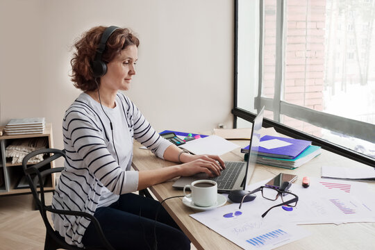A woman of 40-45 years old works in a home office.