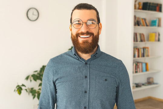 A nice portrait of a young bearded man in a office is smiling at the camera .