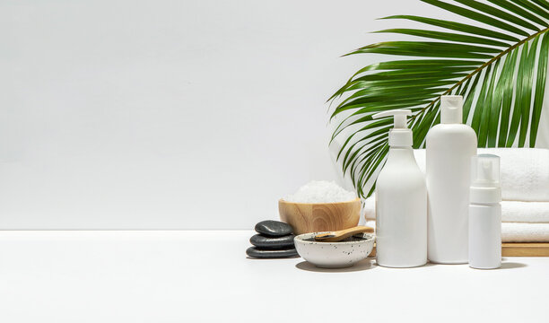 White cosmetic bottles with spa element and towel with palm leaf on white background. Blank label for branding mock-up. Natural beauty product concept. Copy space.