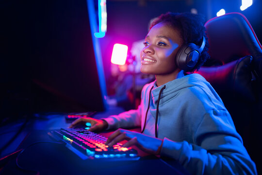 Professional Streamer African young woman cyber gamer studio room with personal computer armchair, keyboard in neon color blur background