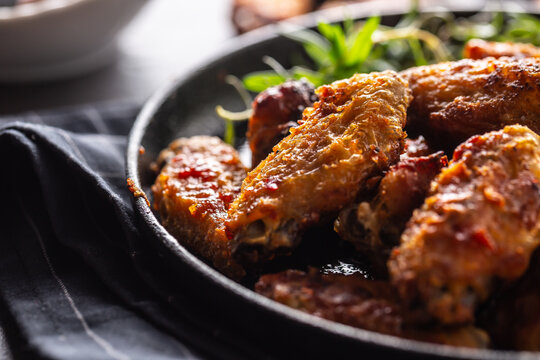 Chicken wings barbeque in a cast iron baking dish with BBQ sauce and rosemary