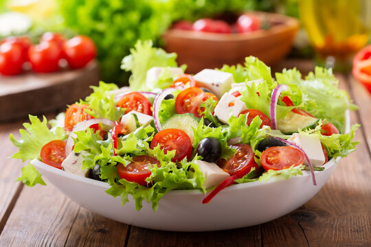 Bowl of fresh salad with vegetables, feta cheese and olives on a wooden table