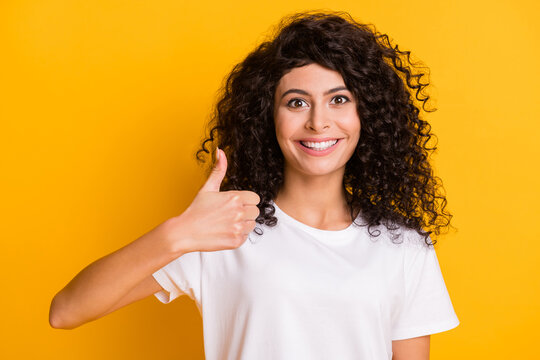 Photo portrait of happy smiling curly girl showing like sign advising promoting isolated on vivid yellow color background