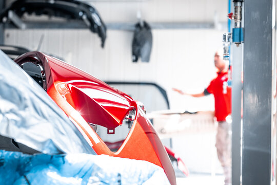 Expert mechanic during the paint job. New color, car repair service, maintenance facility, garage. Red glossy coating, new bumper, restyling, automotive concept, job occupation, production line.