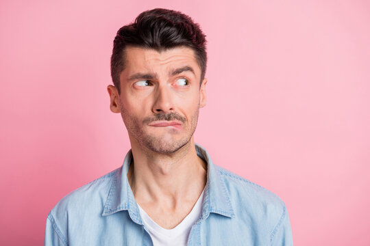 Photo of displeased brunette young man look empty space bite teeth lips isolated on pastel pink color background