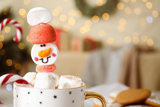 Funny marshmallow snowman in cup of hot drink against blurred festive lights, closeup. Space for text