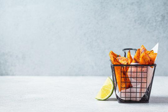 Sweet potato fries in metal basket, gray background. Vegan food concept.