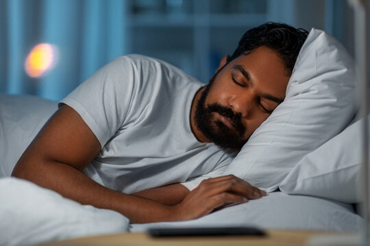 people, bedtime and rest concept - indian man sleeping in bed at home at night