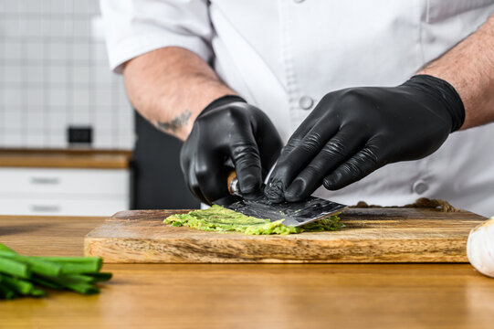 A chef in black gloves prepares guacamole from fresh avacado Hass