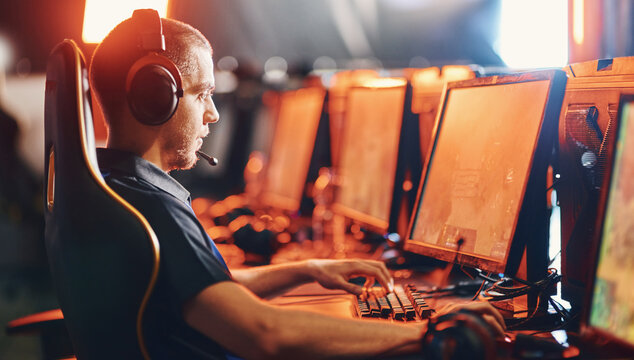 Side view of a focused male professional gamer wearing headphones participating in eSport tournament, looking at PC screen and playing online video game